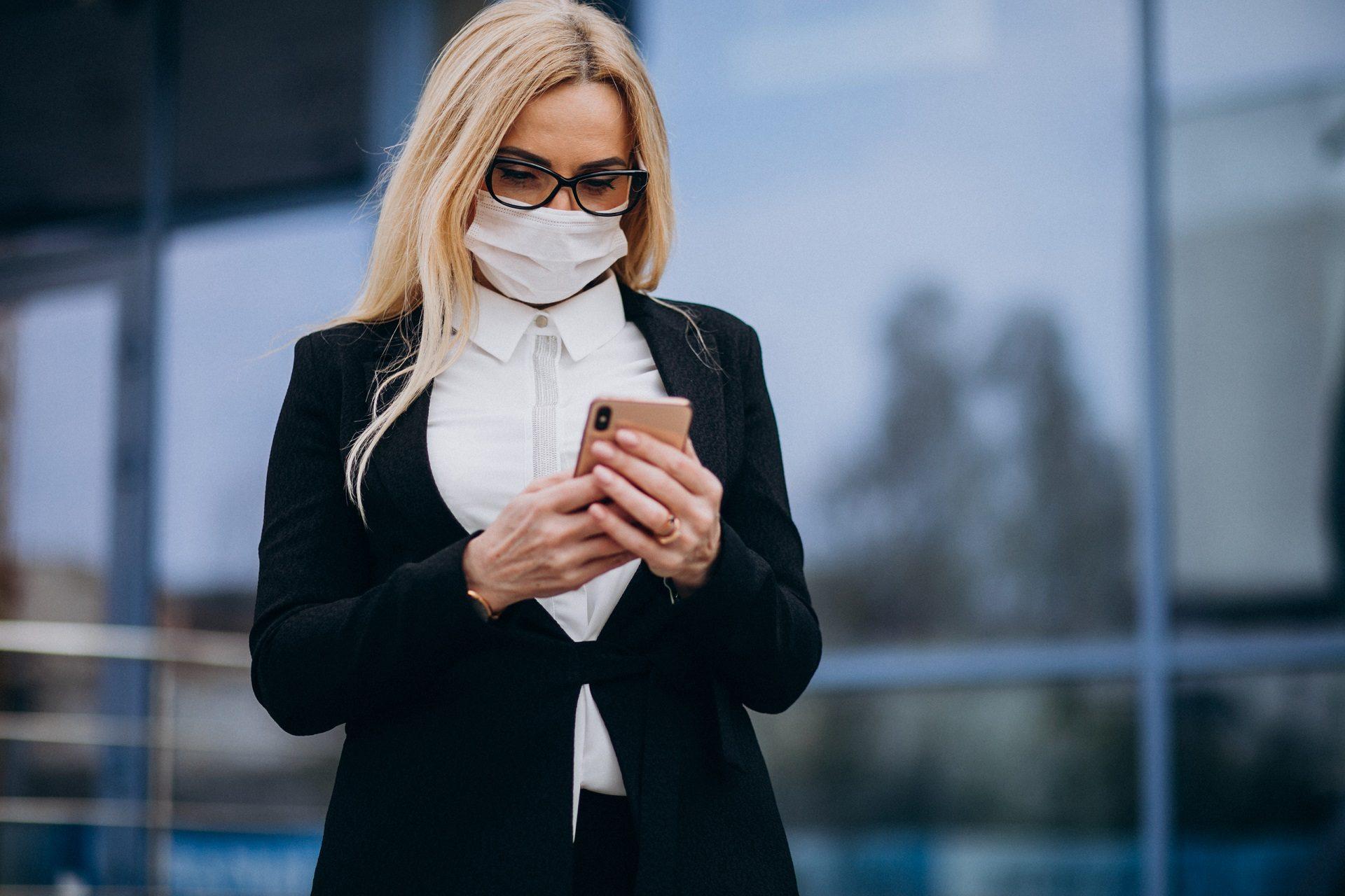 Mulher com máscara e smartphone