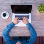 homem usando notebook com um café ao lado